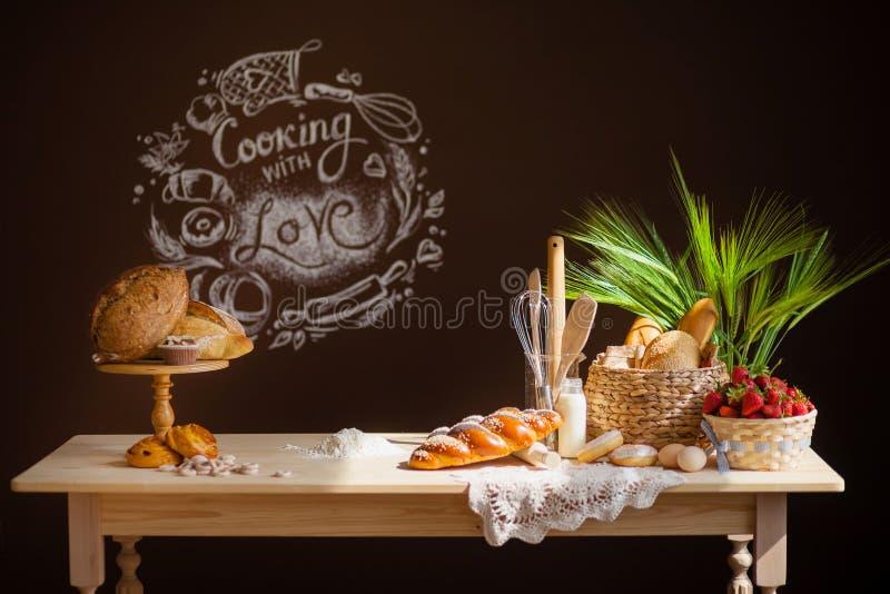 La tabla de madera de la cocina en un fondo marrón, en la tabla es pan, bollos, molletes, una cesta de fresas fotos de archivo