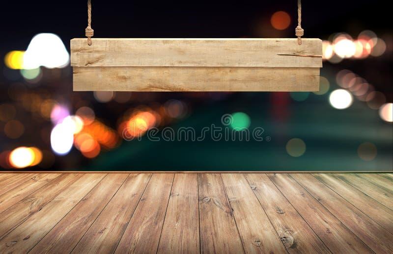 La tabla de madera con el colgante de la muestra de madera en ciudad enciende el fondo borroso noche fotos de archivo