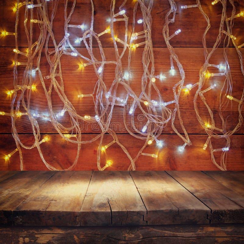 La tabla de madera del tablero delante de la guirnalda caliente del oro de la Navidad se enciende en fondo rústico de madera Imag imagen de archivo libre de regalías