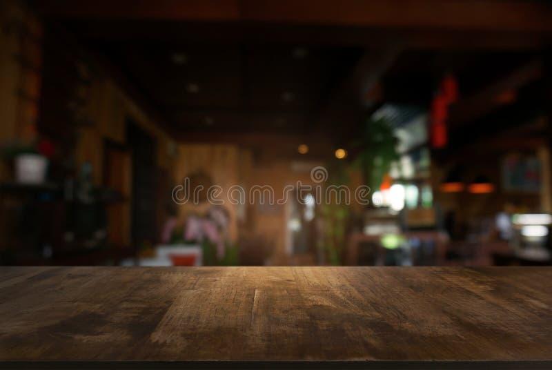 La tabla de madera oscura vacía delante del extracto empañó el fondo fotografía de archivo