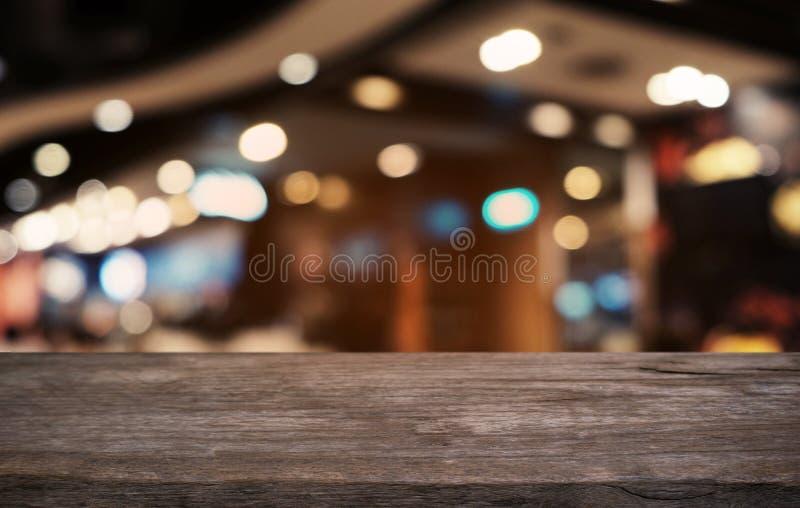 La tabla de madera oscura vacía delante del extracto empañó el fondo del bokeh del restaurante Puede ser utilizado para la exhibi foto de archivo