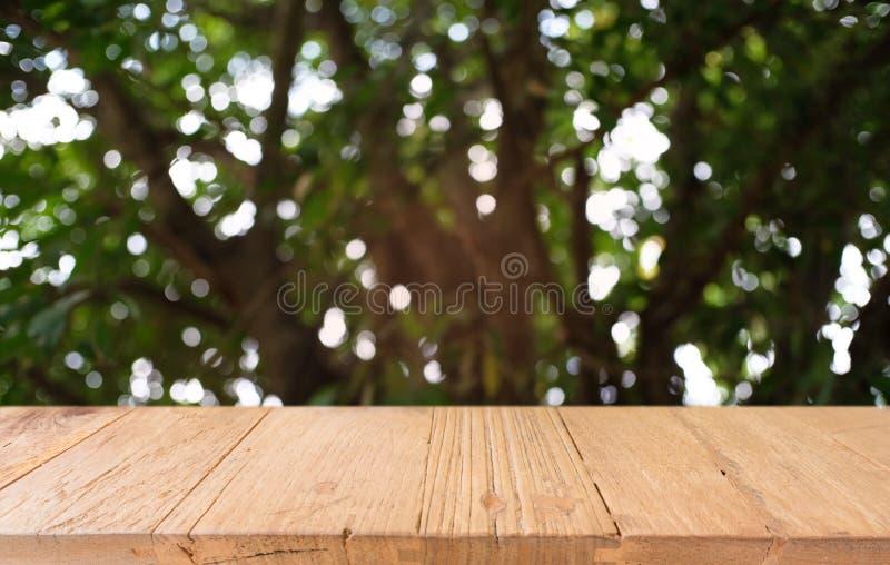 La tabla de madera oscura vacía delante del extracto empañó el fondo del bokeh del restaurante Puede ser utilizado para la exhibi fotos de archivo