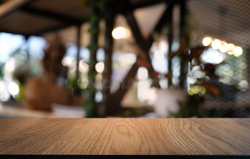La tabla de madera oscura vacía delante del extracto empañó el fondo del bokeh del restaurante Puede ser utilizado para la exhibi foto de archivo libre de regalías