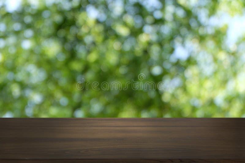 La tabla de madera oscura vacía delante del extracto empañó el fondo del bokeh del restaurante imagen de archivo libre de regalías