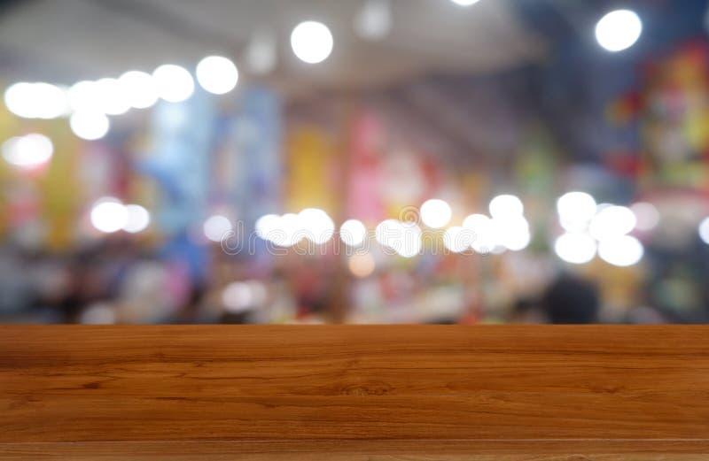 La tabla de madera oscura vacía delante del extracto empañó el fondo del interior del café y de la cafetería Puede ser utilizado  fotos de archivo