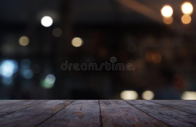 La tabla de madera oscura vacía delante del extracto empañó el fondo del interior del café y de la cafetería Puede ser utilizado  foto de archivo