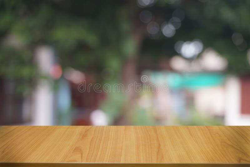 La tabla de madera oscura vac?a delante del extracto empa?? el fondo del bokeh del restaurante fotos de archivo