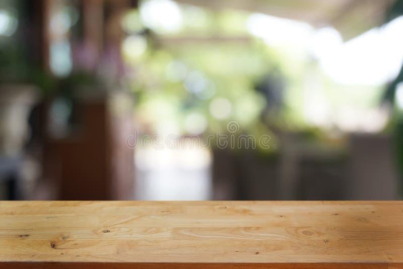 La tabla de madera oscura vac?a delante del extracto empa?? el fondo del bokeh del restaurante foto de archivo