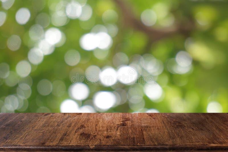 La tabla de madera oscura vac?a delante del extracto empa?? el fondo del bokeh del restaurante imagenes de archivo