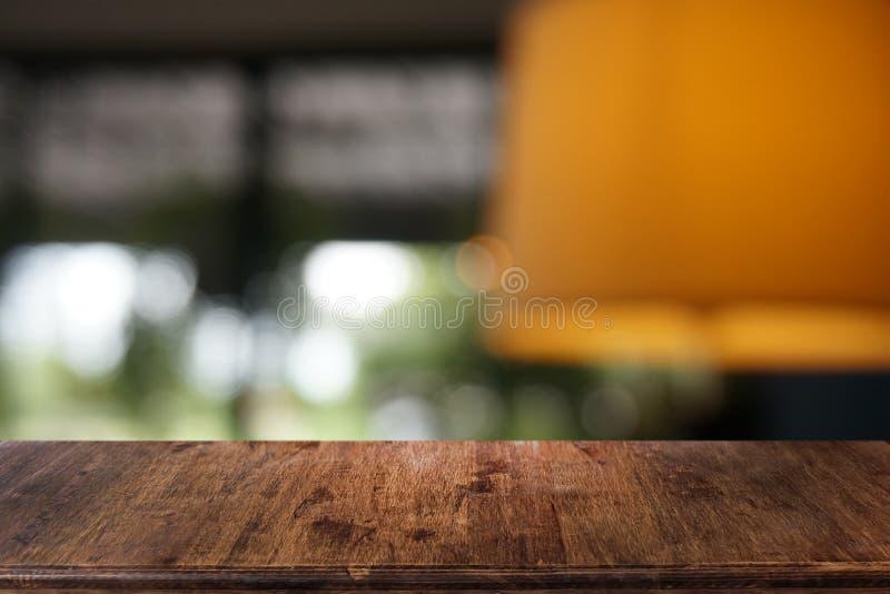 La tabla de madera oscura vac?a delante del extracto empa?? el fondo del bokeh del restaurante fotografía de archivo libre de regalías