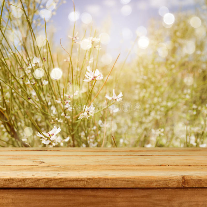La tabla de madera vacía de la cubierta durante verano borroso del bokeh florece el fondo para el montaje del producto foto de archivo