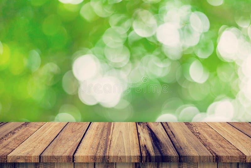 La tabla de madera vacía y el bokeh verde borroso extracto sale de la textura del fondo, montaje de la exhibición con el espacio  fotografía de archivo