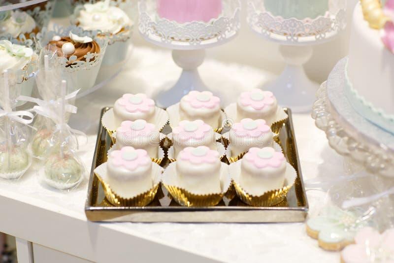 La tabla dulce elegante con la torta grande, magdalenas, torta hace estallar en cena imagen de archivo libre de regalías