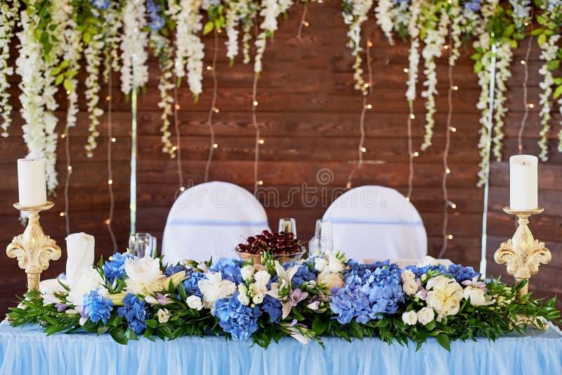 La tabla es joven, en el fondo de una pantalla de madera, adornado con una guirnalda de flores en azul y blanco imagen de archivo libre de regalías