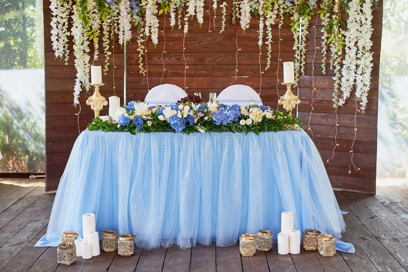 La tabla es joven, en el fondo de una pantalla de madera, adornado con una guirnalda de flores en azul y blanco fotos de archivo
