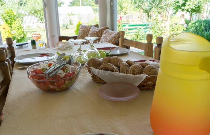 La tabla festiva sirvió platos y adornada Almuerzo en el aire abierto Jarra anaranjada de agua y de flores Ensalada y comida en fotografía de archivo libre de regalías