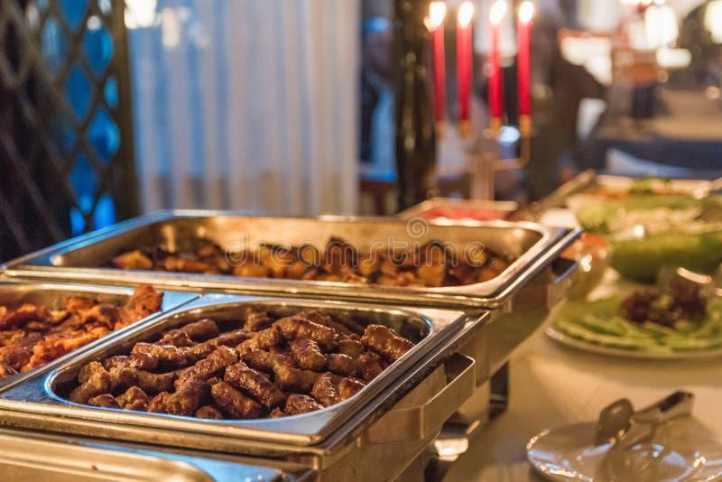 La tabla llena con toda clase de comida Comenzó con la carne fresca, el queso, las aceitunas y cuatro velas en fondo foto de archivo
