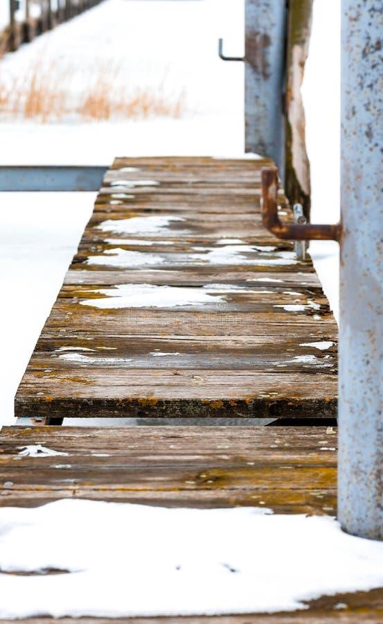 La tabla o el puente de madera del piso cubrió nieve imagen de archivo