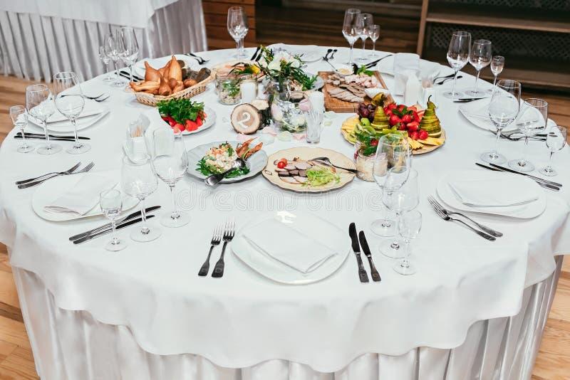La tabla redonda del restaurante sirvió el lujo para la cena festiva imagen de archivo libre de regalías