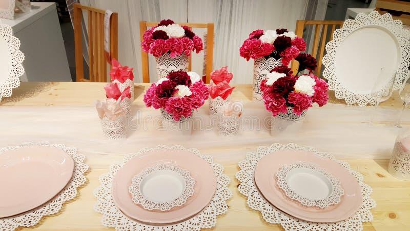 La tabla romántica fijó con el plato rosado y las flores rosadas imagen de archivo