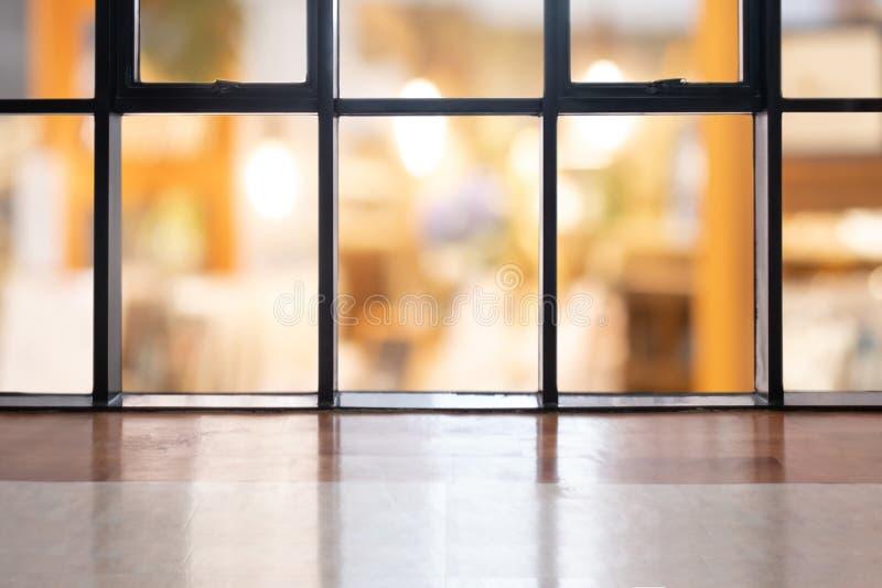 La tabla vacía del piso de madera de la perspectiva en el top sobre fondo borroso de la cafetería, puede ser falsa usado para arr foto de archivo