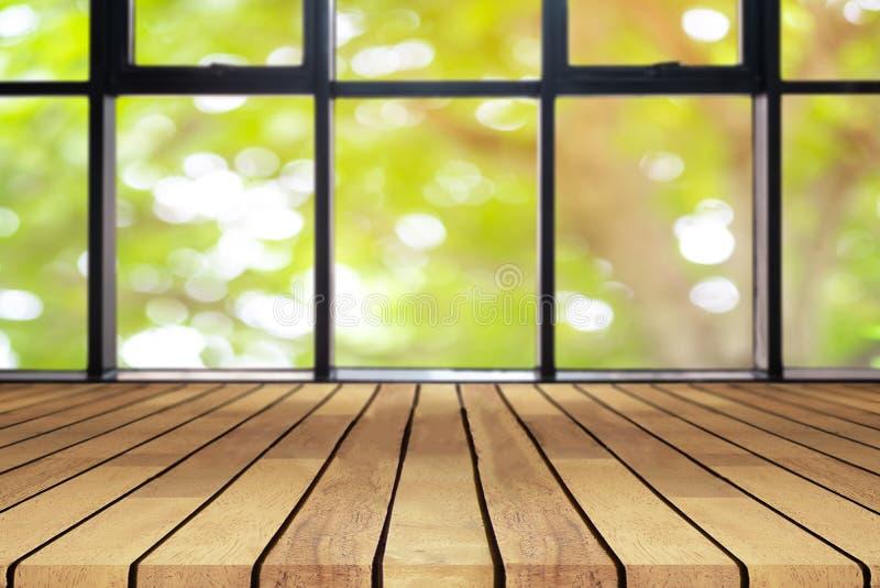 La tabla vacía del tablero de madera de la perspectiva en el top sobre fondo natural borroso, puede ser falsa usado para arriba p imagen de archivo libre de regalías