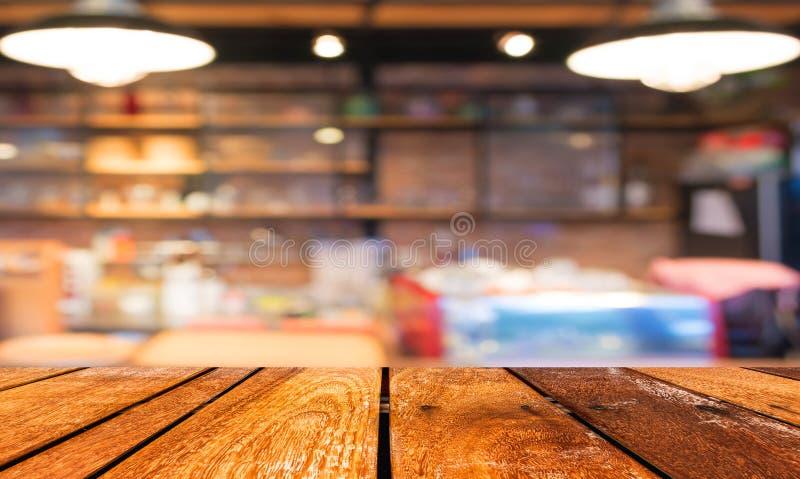 La tabla y la cafetería de madera vacías empañan el fondo con el imag del bokeh foto de archivo