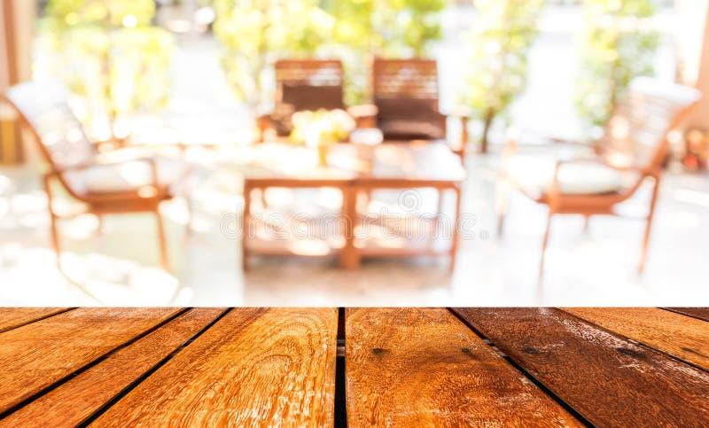 La tabla y la cafetería de madera vacías empañan el fondo con el imag del bokeh imagen de archivo