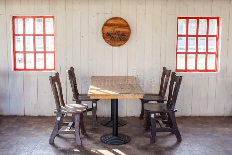 La tabla y las sillas de madera viejas adornan en restaurante con la ventana roja en la pared blanca en el fondo imagenes de archivo