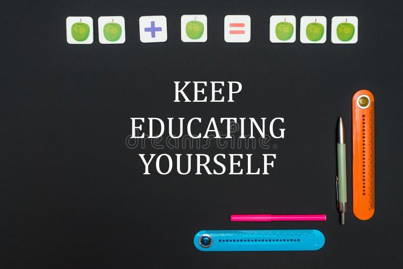 La table d'art noir avec des approvisionnements de papeterie avec des mots gardent l'éducation vous-même illustration stock