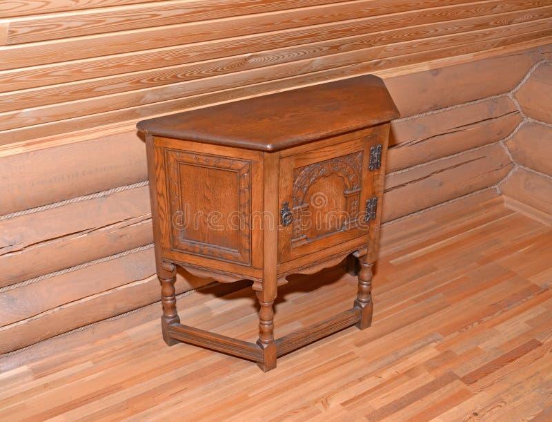 La table de chevet en bois se tient près d'un mur boisé image stock