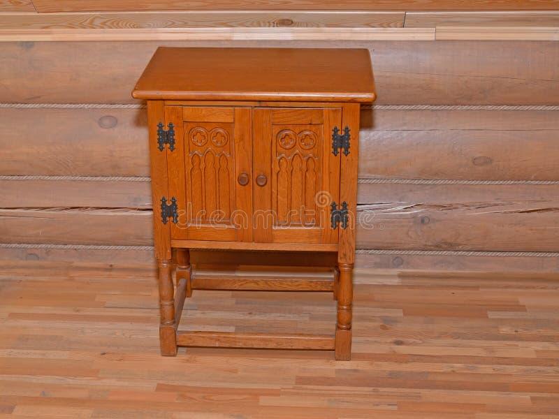 La table de chevet en bois se tient près d'un mur boisé photo libre de droits
