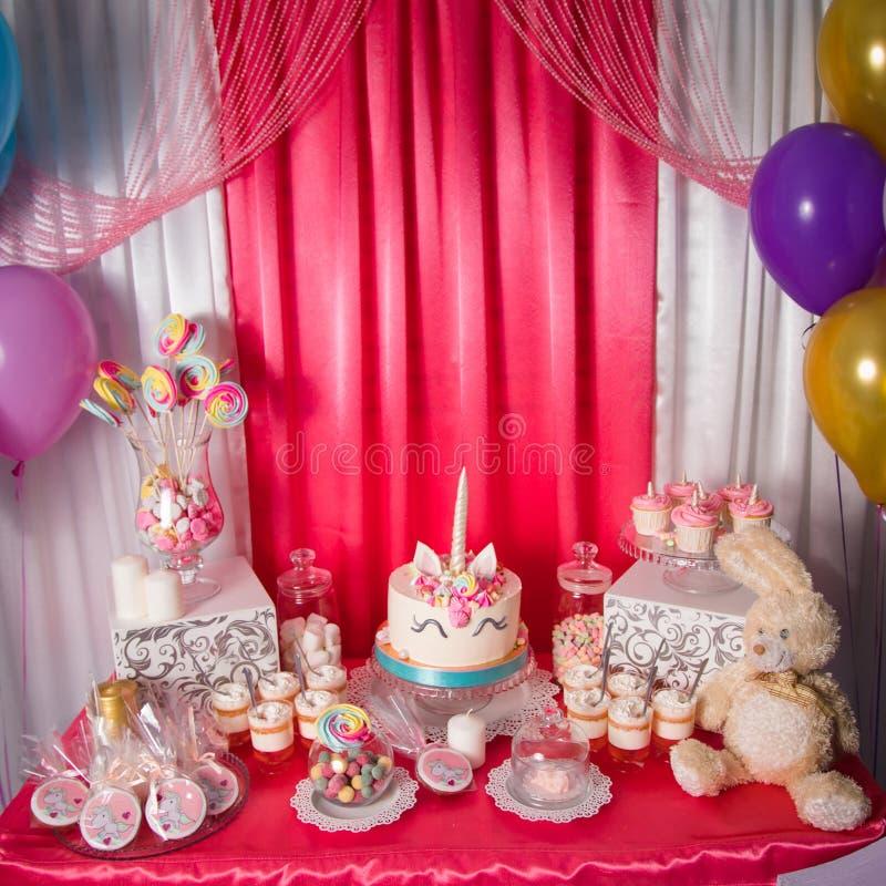 La table douce et la grande licorne durcissent pour le premier anniversaire de bébé La friandise avec beaucoup de sucreries et bo photographie stock