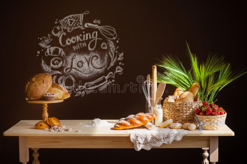 La table en bois de cuisine sur un fond brun, sur la table est pain, des petits pains, les petits pains, un panier des fraises photos stock
