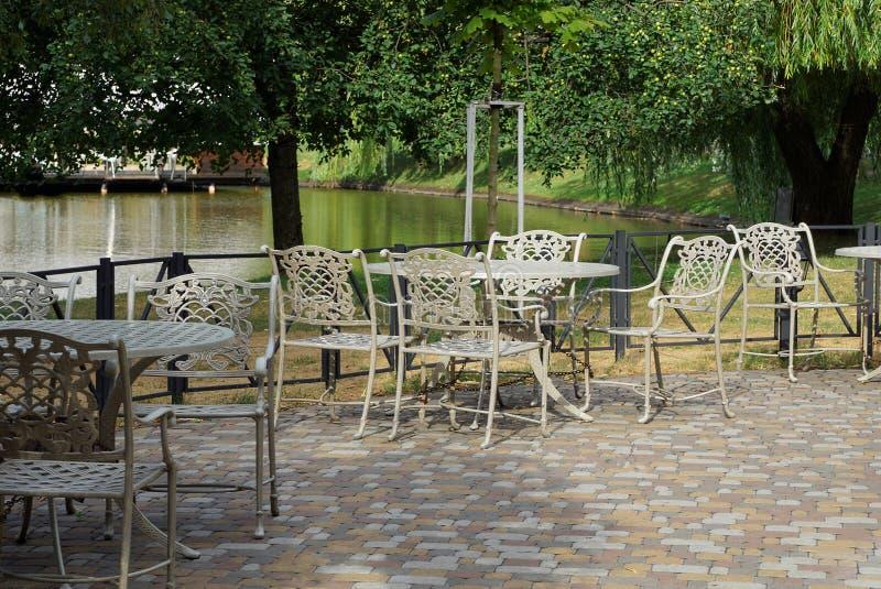 La table et les chaises blanches se tiennent sur la rue sur le trottoir en parc photos stock