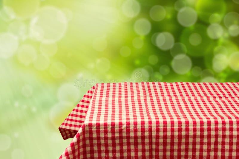 La table vide avec le rouge a vérifié la nappe au-dessus du fond vert de bokeh. photos stock