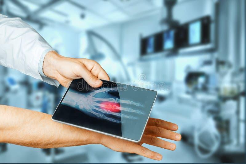 La tableta del doctor Hand With Digital explora la mano paciente, la tecnología moderna de la radiografía en medicina y el concep imagenes de archivo