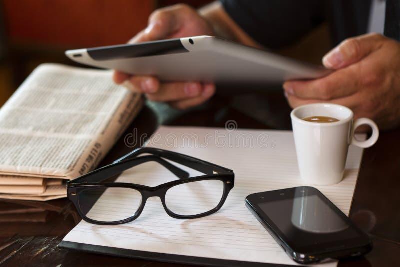 La tableta del periódico del café de la taza da el teléfono fotografía de archivo