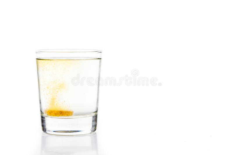 La tableta efervescente de la vitamina C burbujea en el vidrio de agua imágenes de archivo libres de regalías