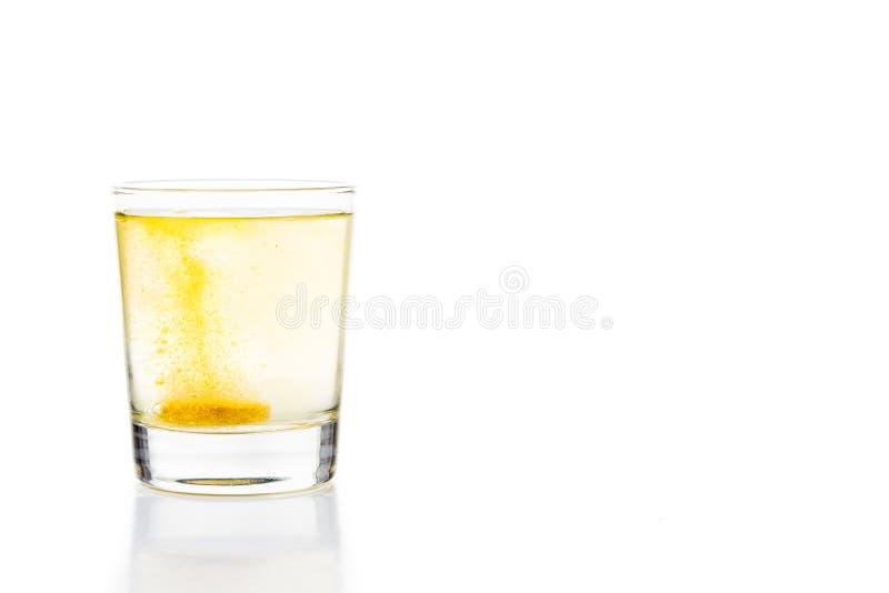 La tableta efervescente de la vitamina C burbujea en el vidrio de agua foto de archivo libre de regalías