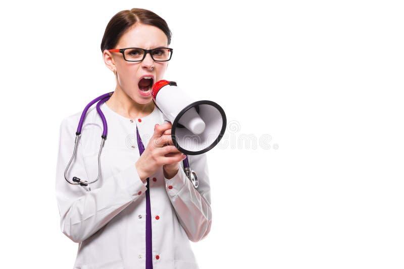 La tableta femenina hermosa joven de la tenencia del doctor en sus manos habla en megáfono en el fondo blanco imágenes de archivo libres de regalías