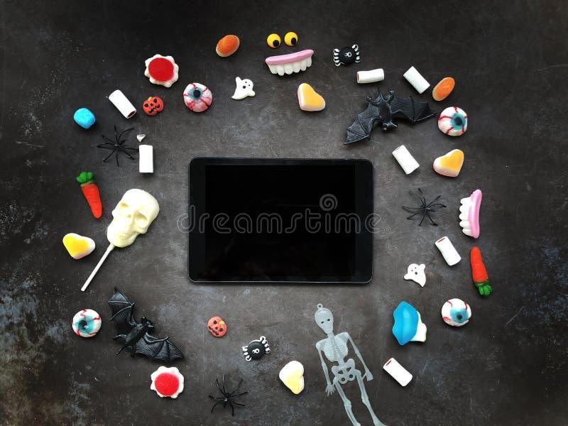 La tableta y el caramelo de Halloween yacen sobre fondo oscuro texturizado foto de archivo