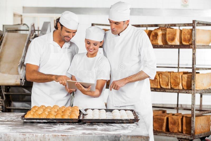 La tablette de utilisation de Baker ensemble dans la boulangerie photographie stock