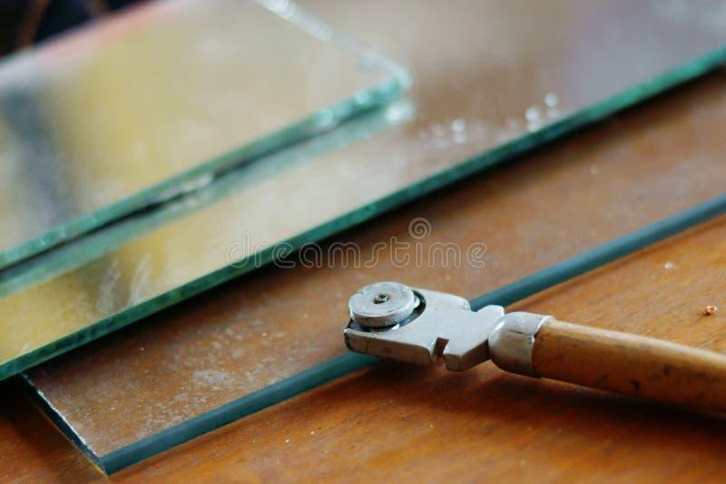 La taglierina di vetro ed il vetro rivestono su fondo di legno immagini stock