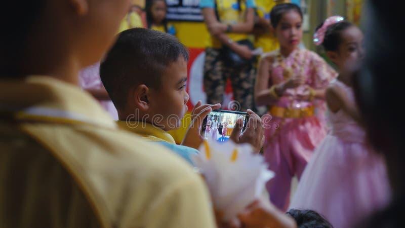 La Tailandia, Koh Samui, il 5 dicembre 2015 Ragazzo che prende le immagini con il telefono di mobil dei bambini che eseguono che  fotografia stock libera da diritti
