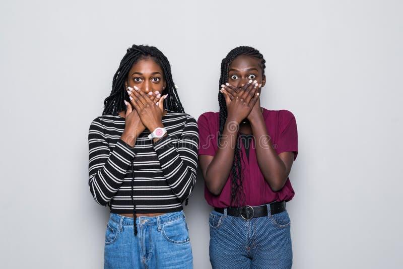 La taille a tiré de choqué deux femmes africaines couvrent des mouthes des deux mains, essayer d'être sans voix dans la situation image stock