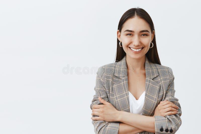 La taille- a tiré de l'entrepreneur féminin heureux sûr dans la veste élégante au-dessus du T-shirt, jugeant des mains croisées s photos libres de droits