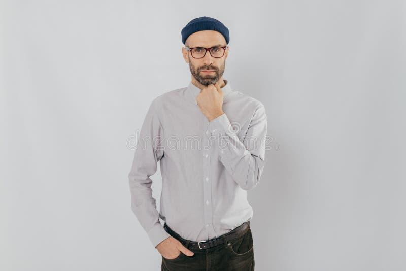 La taille a tiré de l'homme sérieux garde une main sous le menton, l'autre dedans poche, a la chaume, utilise le chapeau, chemise photographie stock libre de droits