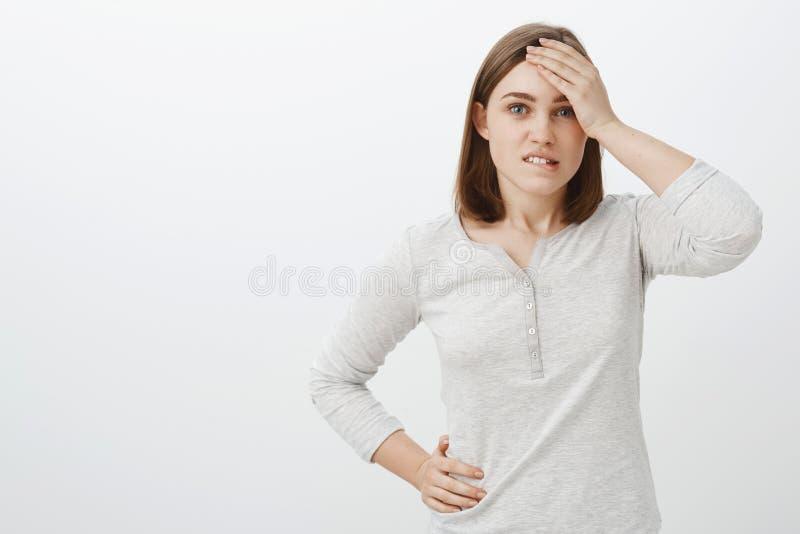 La taille- a tiré du collègue féminin créatif futé dans le chemisier blanc tenant la main sur la lèvre inférieure acérée de front photographie stock
