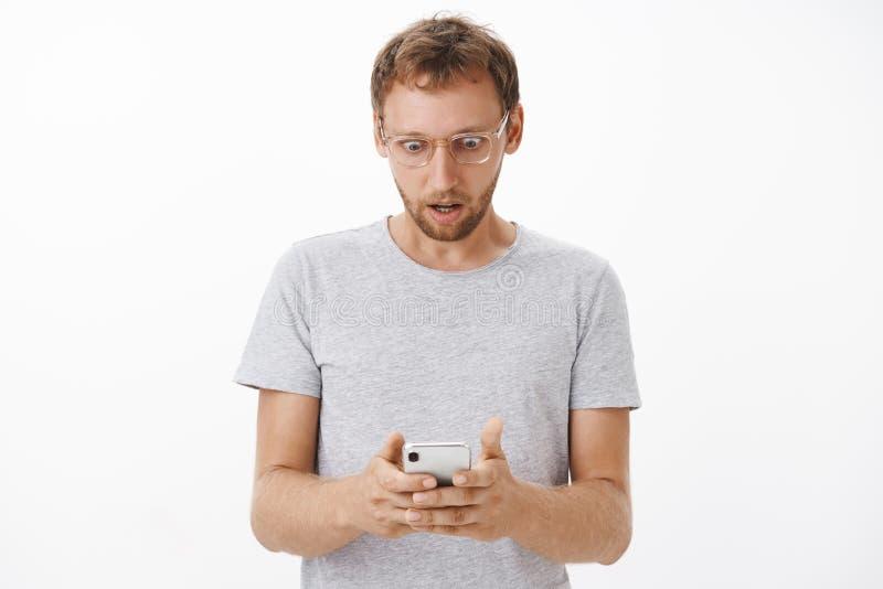 La taille- tirée de l'homme recevant le message choquant regardant fixement avec a secoué aux yeux sautants d'écran de smartphone photo libre de droits